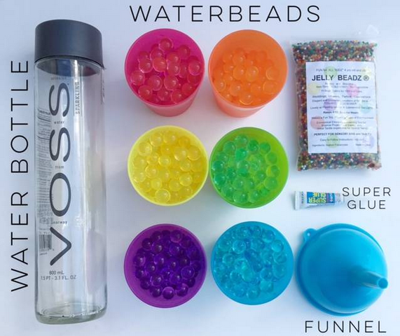 An empty water bottle next to colorful cups of water beads, super glue, and a funnel
