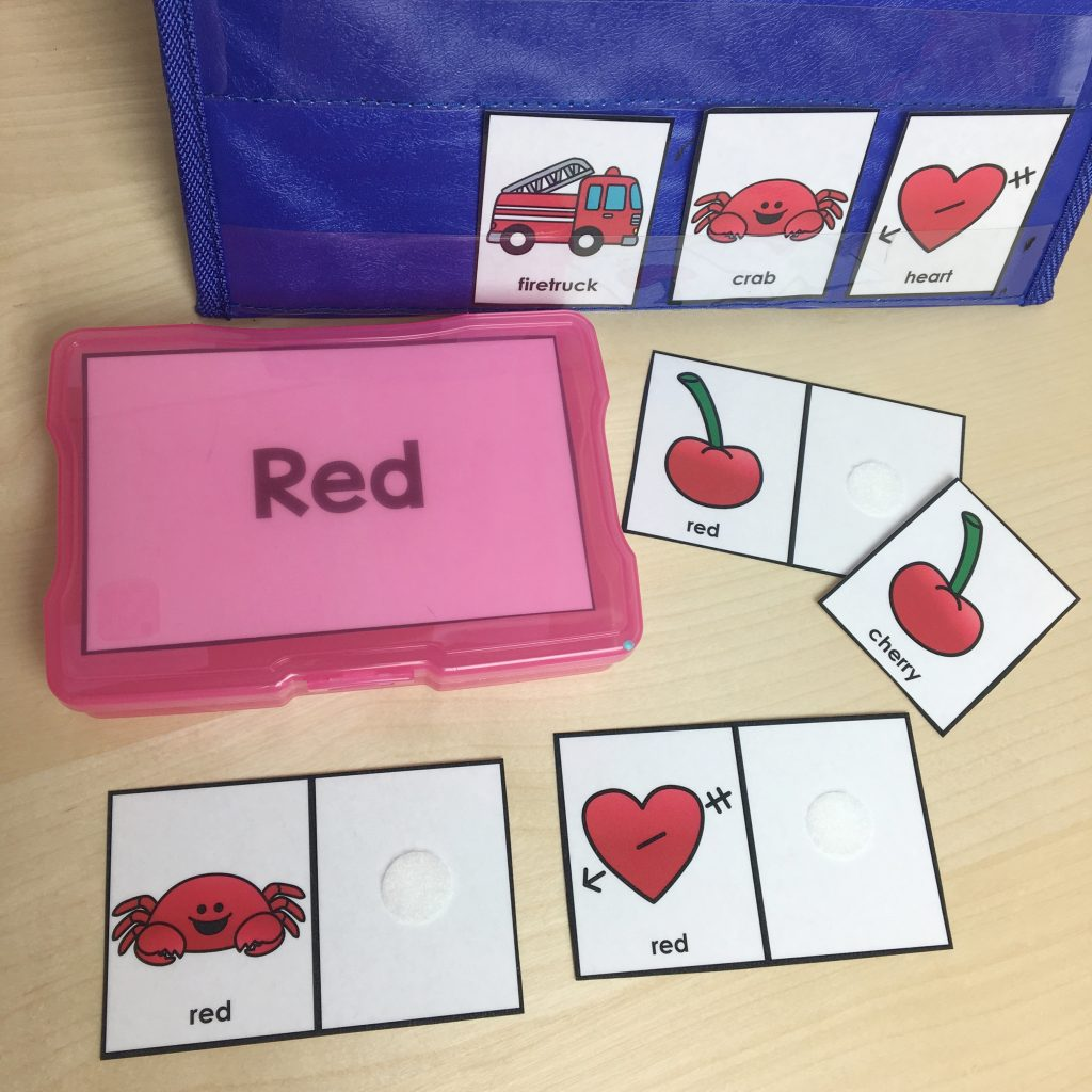 Red plastic box surrounded by cards with red hearts, cherries, and crabs and a blue case in the background