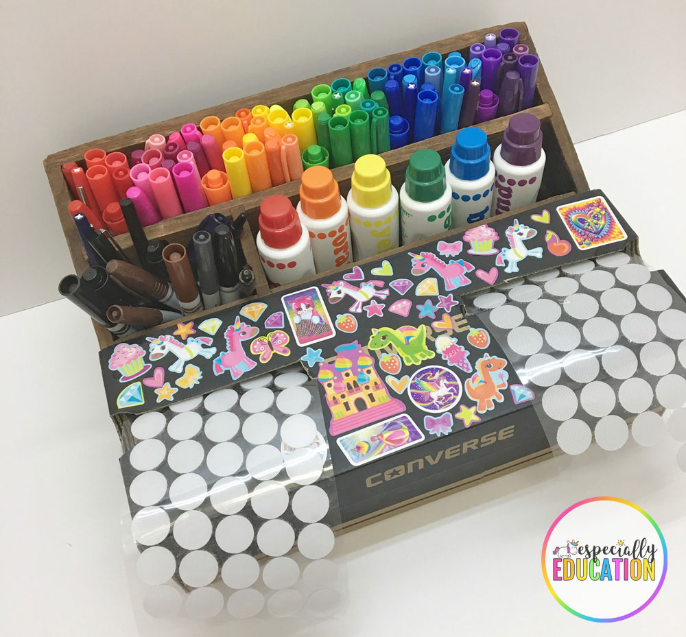 A pencil holder with pens and inks and a cardboard box decorated with fun stickers