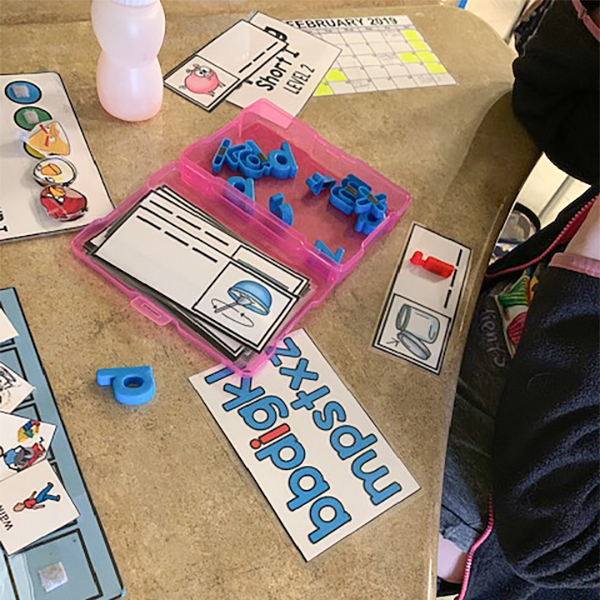 Colorful task box pieces and tokens on a classroom desk