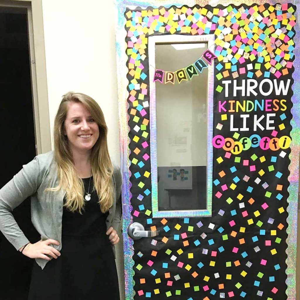 """Young woman teacher standing in front of her decorated door that says """"Throw kindness like confetti."""""""